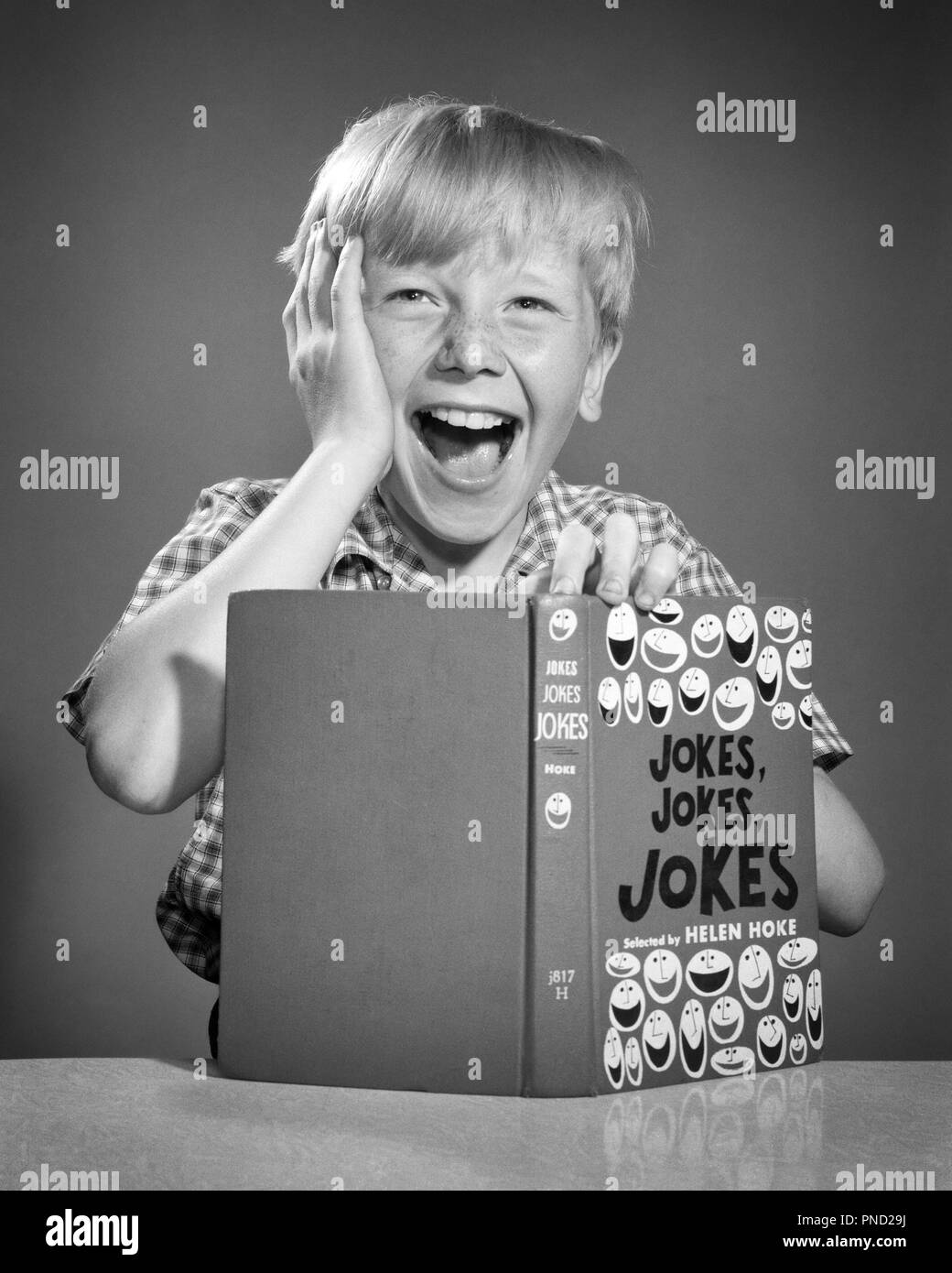 1950s BLOND BOY HOLDING HAND TO HEAD LAUGHING OUT LOUD LOOKING AT CAMERA READING BOOK FULL OF JOKES - j6441 DEB001 HARS JOY LIFESTYLE STUDIO SHOT HOME LIFE HALF-LENGTH INSPIRATION MALES FRECKLES ENTERTAINMENT EXPRESSIONS B&W EYE CONTACT SUCCESS HAPPINESS HEAD AND SHOULDERS CHEERFUL DISCOVERY YOUNG MAN EXCITEMENT TELLING COMEDIAN OF OPPORTUNITY SMILES CONCEPTUAL COMEDY IMAGINATION JOYFUL OVER THE TOP DEB001 GROWTH IDEAS JUVENILES RELAXATION RIOTOUS BLACK AND WHITE CAUCASIAN ETHNICITY JOKE OLD FASHIONED - Stock Image