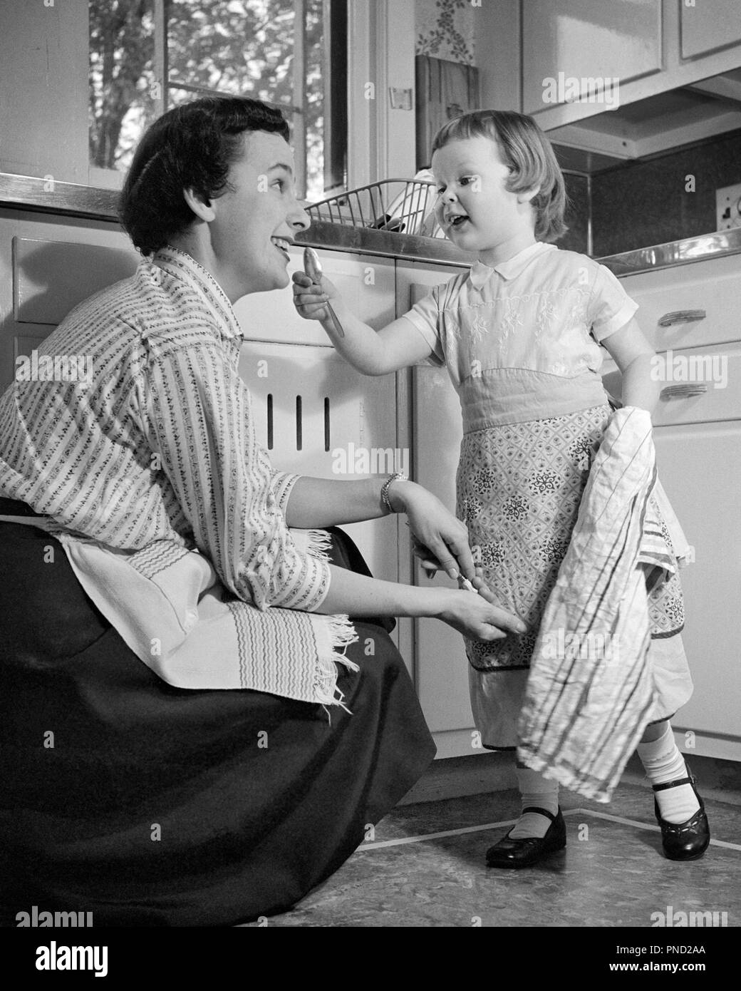 1950s LITTLE GIRL AND MOTHER IN KITCHEN BOTH WEARING APRONS GIRL HOLDING DISH TOWEL GESTURING TO MOTHER - j8225 HBB001 HARS OLD TIME BUSY NOSTALGIA GOOD OLD FASHION 1 TOWEL JUVENILE STYLE COMMUNICATION LAUGH DISH TEAMWORK PLEASED JOY LIFESTYLE FEMALES HEALTHINESS HOME LIFE FULL-LENGTH LADIES DAUGHTERS PERSONS CARING CONFIDENCE GESTURING APRONS B&W HOMEMAKER HAPPINESS HOMEMAKERS CHEERFUL BOTH AND EXCITEMENT MARY JANE HOUSEWIVES SMILES CONNECTION HELPFUL JOYFUL STYLISH THUMBS UP BEHAVIOR GROWTH JUVENILES MID-ADULT MID-ADULT WOMAN MOMS TOGETHERNESS BLACK AND WHITE CAUCASIAN ETHNICITY - Stock Image