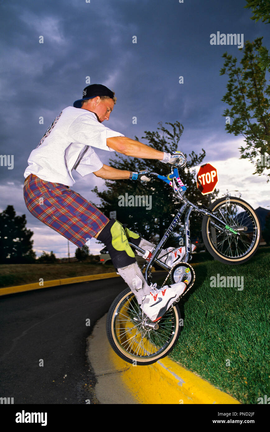 1990s YOUNG MAN WEARING WHITE TEE SHIRT AND SHORTS WITH KNEE PADS JUMPING BICYCLE UP ON CURB - kb29899 WAL004 HARS PAD STOP HEALTHY BALANCE KNEE SAFETY COMPETITION STRONG ATHLETE FIT JOY LIFESTYLE BIKING TIRE COPY SPACE FULL-LENGTH DANGER MALES RISK TEENAGE BOY ATHLETIC PLAID PEDAL TRANSPORTATION FREEDOM GUY RUSH SKILL NEIGHBORHOOD AEROBIC HIP LEISURE STRENGTH STUNT SNEAKER AEROBIC EXERCISE EXPERIENCED YOUNG MAN EFFORT EXCITEMENT RECREATION INNOVATION GRIP ON BICYCLING MASCULINE FEARLESS SKILLFUL RECREATION BICYCLING BASEBALL HAT CULTURE STYLISH CURB SKILLED STOP SIGN T-SHIRT FREESTYLE TRICKY - Stock Image