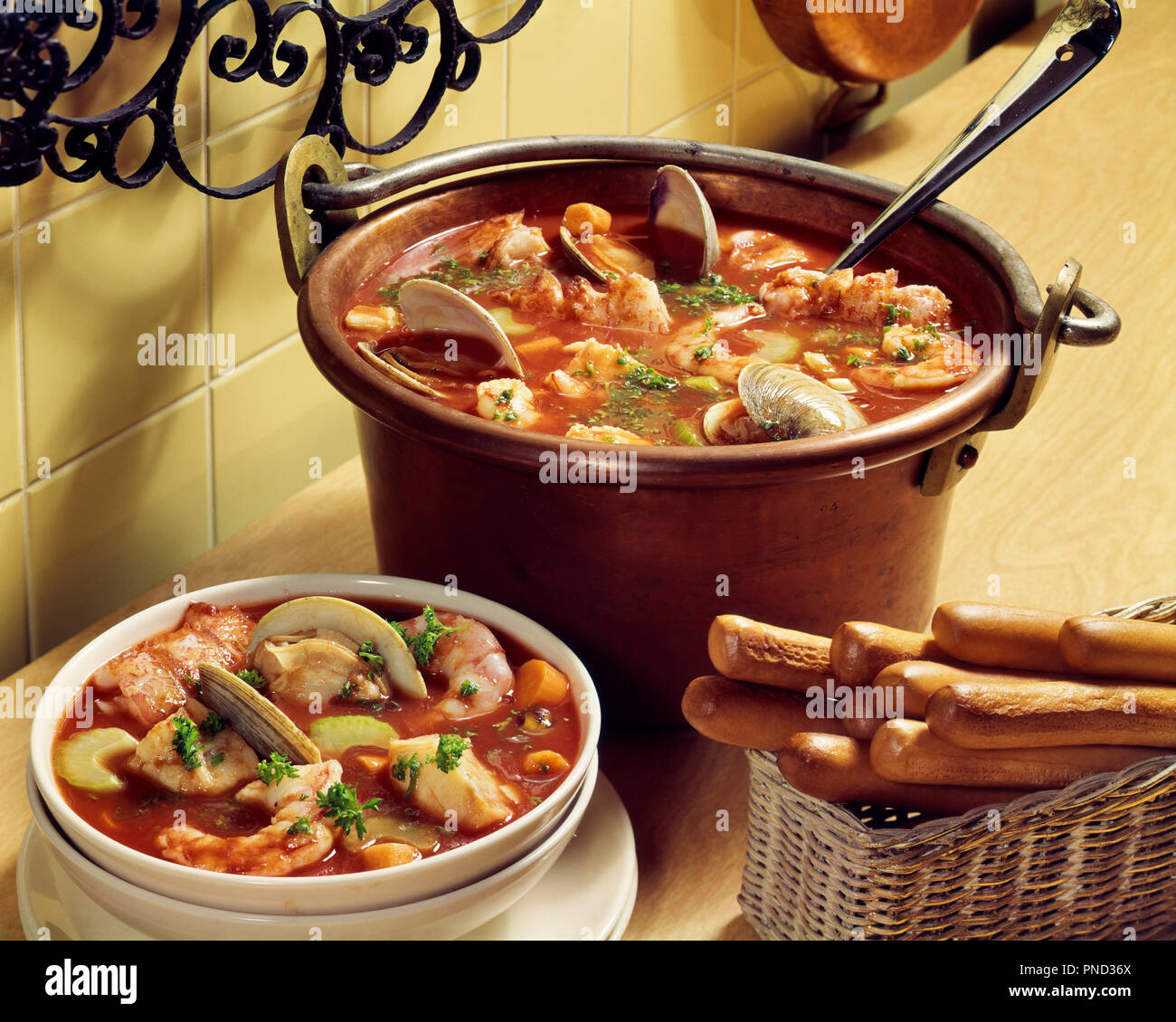 1980s SEAFOOD STEW IN COPPER POT SINGLE SERVING IN A BOWL WITH BREAD STICKS ALONG SIDE - kf21255 PHT001 HARS SEAFOOD - Stock Image