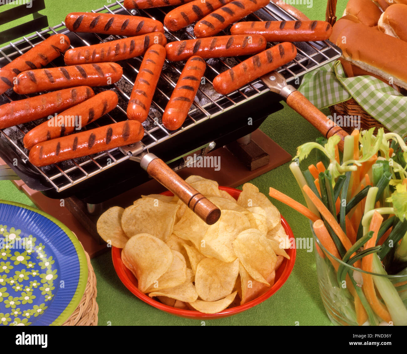 1970s 1980s GRILLED HOT DOGS ON HIBACHI CHARCOAL GRILL ALONG WITH BUNS POTATO CHIPS SLICED CELERY STALKS AND CARROT STICKS - kf24067 FRT001 HARS POTATO CHIPS - Stock Image