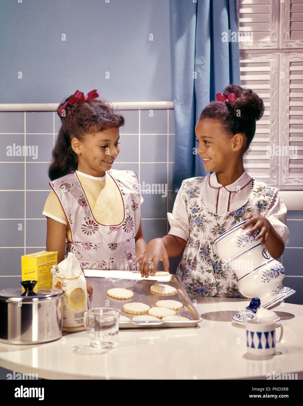 1960s Two Smiling African American Girls Sisters In Kitchen Baking