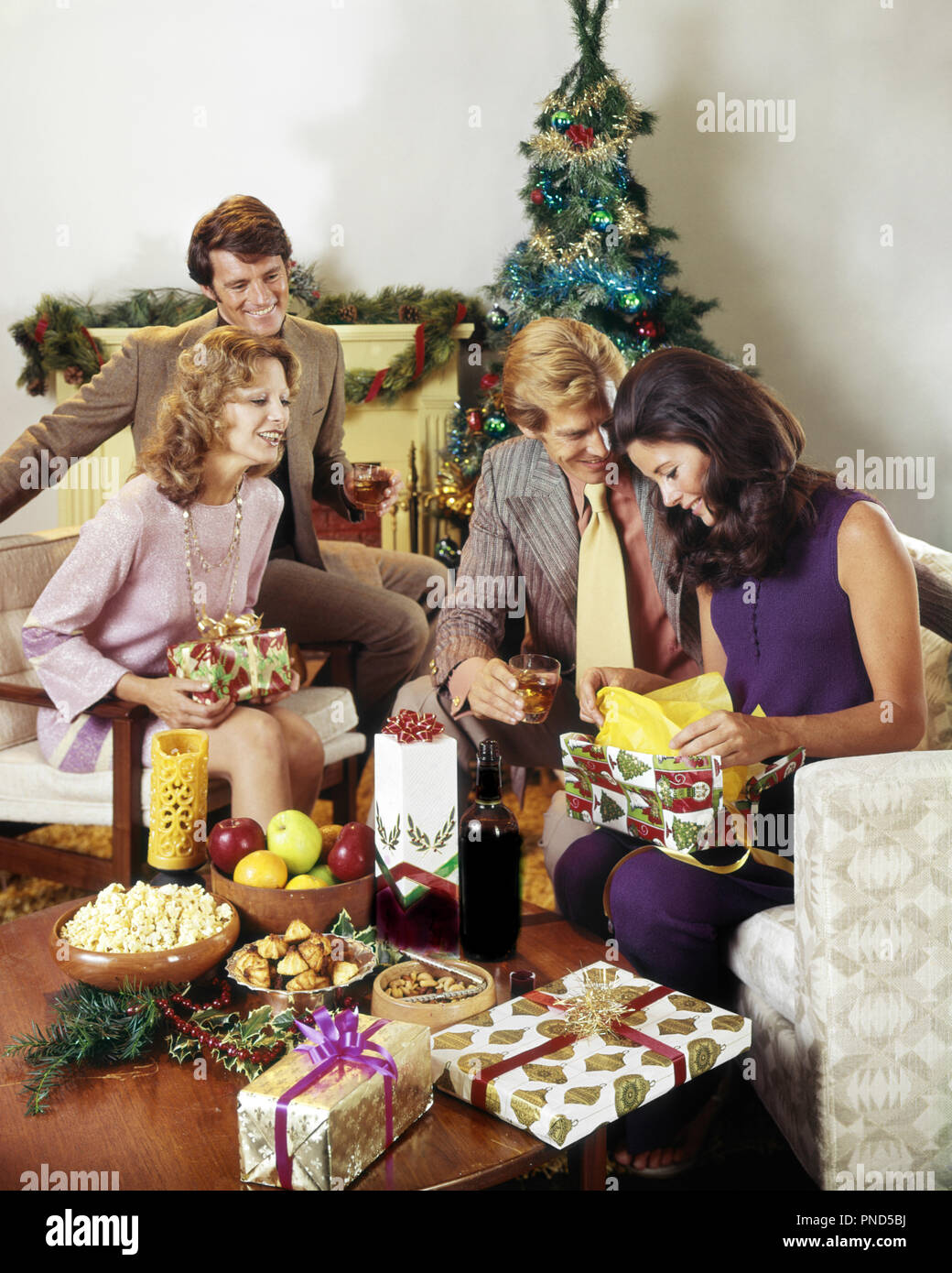 1970s TWO COUPLES EXCHANGING GIFTS AROUND CHRISTMAS TREE DRINKING ...