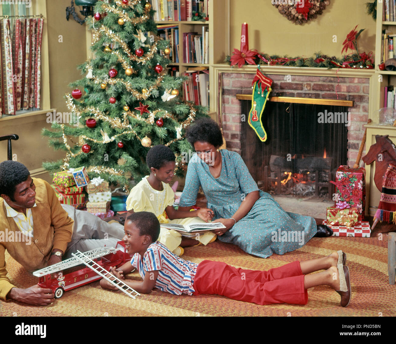 1970s AFRICAN AMERICAN FAMILY OF FOUR ON LIVING ROOM FLOOR PLAYING WITH CHRISTMAS TOYS AND PRESENTS - kx8042 PHT001 HARS COUPLES HUSBAND 3 FIREPLACE DAD FOUR MOM INDOORS FLOOR NOSTALGIC PAIR 4 SUBURBAN XMAS COLOR RELATIONSHIP MOTHERS OLD TIME NOSTALGIA OLD FASHION 1 JUVENILE STOCKING PEACE WREATH SONS FAMILIES JOY LIFESTYLE CELEBRATION FEMALES MARRIED SPOUSE HUSBANDS GROWNUP HOME LIFE COPY SPACE FULL-LENGTH LADIES DAUGHTERS PERSONS INSPIRATION GROWN-UP CARING MALES GIFTS FATHERS WINTERTIME WINTER SEASON STRUCTURE HAPPINESS STRENGTH LIVING ROOM AFRICAN-AMERICAN CHOICE DADS EXCITEMENT TRIO - Stock Image