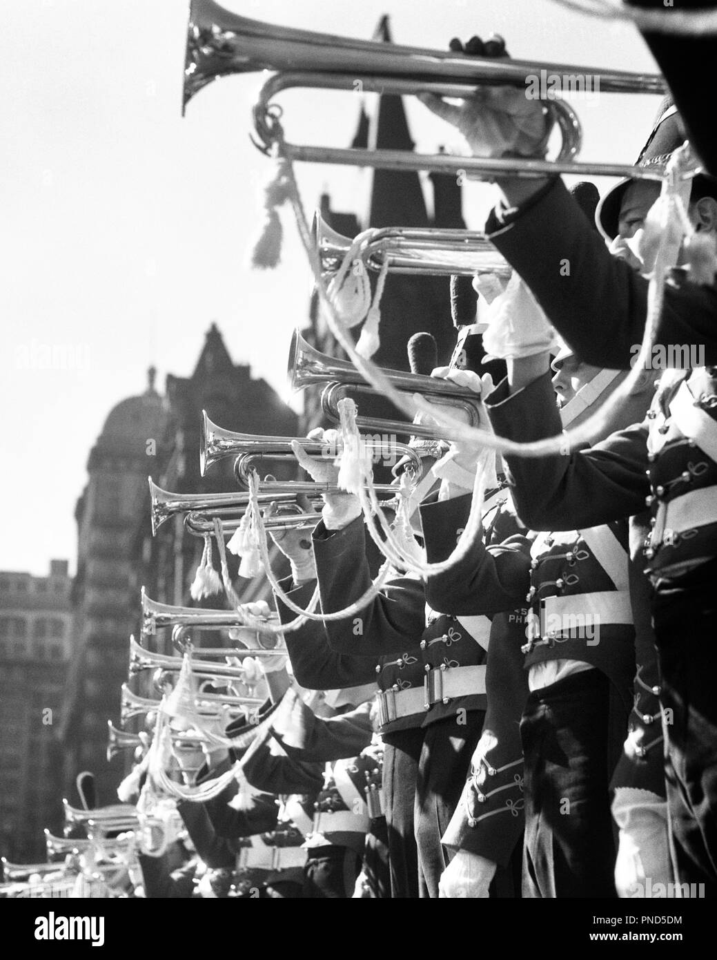 1930s MUSICAL INSTRUMENTS MARCHING MILITARY BRASS BAND IN UNIFORMS HERALDING PLAYING FLOURISHES ON BUGLES - m4476 HAR001 HARS B&W HORNS FREEDOM PERFORMING OCCUPATION HAPPINESS UNIVERSITIES CAREERS LOUD LOW ANGLE PRIDE ON OCCUPATIONS HERALDING HIGHER EDUCATION CADETS COLLEGES BUGLE SYMBOLIC COOPERATION CORPS PAGEANTRY PLAYED PRECISION TOGETHERNESS YOUNG ADULT MAN BLACK AND WHITE BUGLES CEREMONIAL HAR001 OLD FASHIONED PARADES REPRESENTATION TRUMPETS - Stock Image