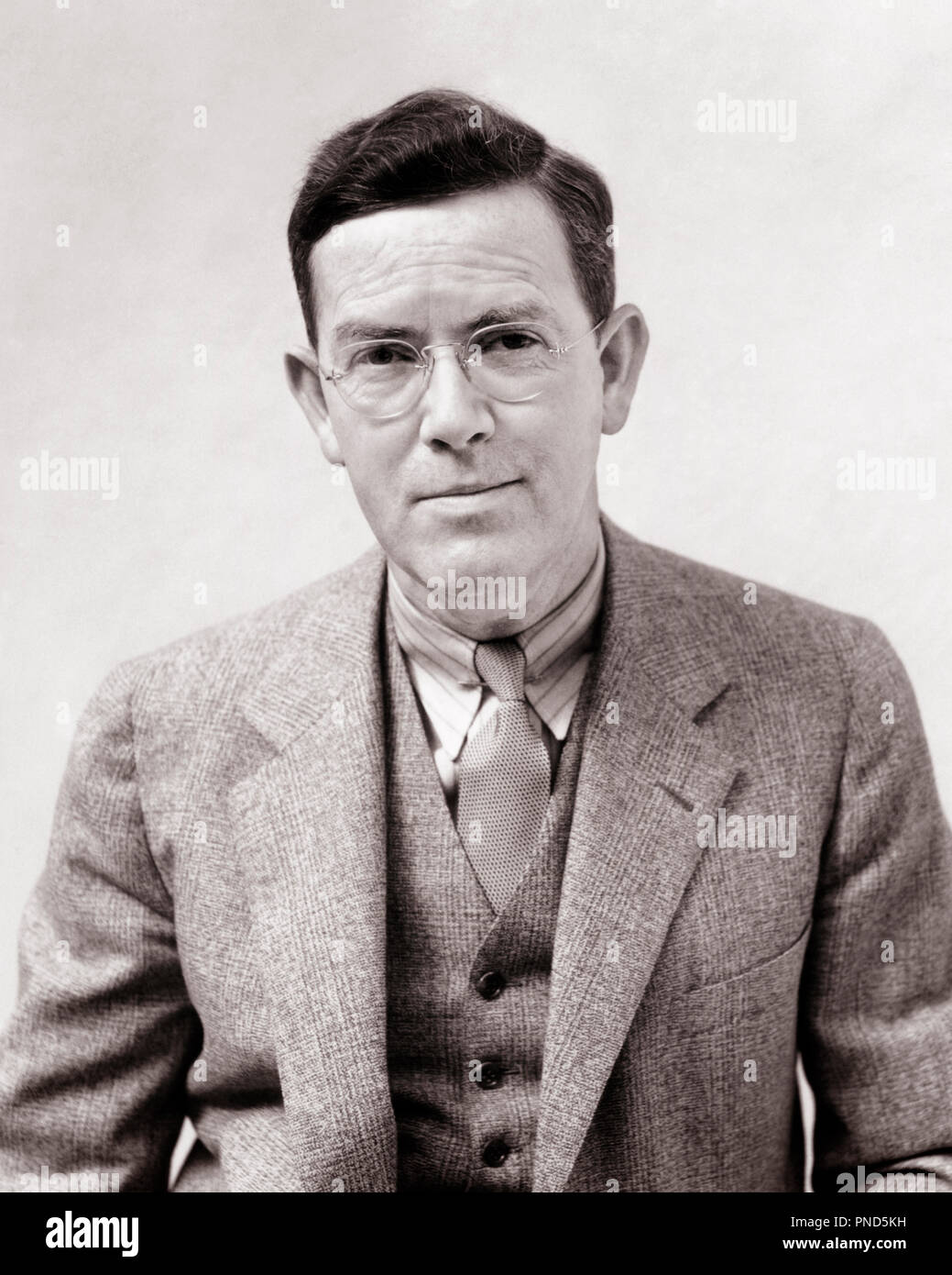 1930s PORTRAIT MAN PHOTOGRAPHER H. ARMSTRONG ROBERTS WEARING GLASSES SUIT VEST TIE LOOKING AT CAMERA - p5505 HAR001 HARS EYE CONTACT HAPPINESS STYLES SMILES THREE PIECE SUIT H ARMSTRONG ROBERTS JOYFUL STYLISH FASHIONS BLACK AND WHITE CAUCASIAN ETHNICITY HAR001 OLD FASHIONED - Stock Image