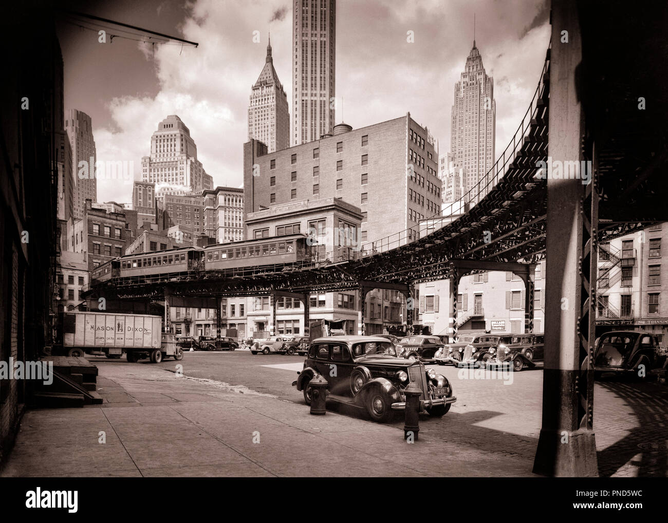 1930s DOWNTOWN FINANCIAL DISTRICT CURVE OF THIRD AVENUE ELEVATED TRAIN AT COENTIES SLIP NEW YORK CITY USA - q36042 CPC001 HARS ELEVATED VEHICLES EDIFICE NEW YORK CITY RAILROADS BLACK AND WHITE CURVE DISTRICT EAST SIDE EL FINANCIAL DISTRICT OLD FASHIONED SKYSCRAPERS - Stock Image