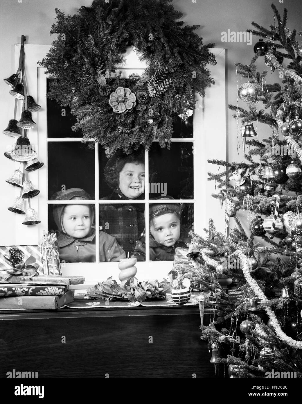 1950s CHILDREN ONE GIRL TWO BOYS LOOKING THROUGH WINDOW AT CHRISTMAS TREE WITH WRAPPED GIFTS WREATH HANGING ABOVE - x325 HAR001 HARS NOSTALGIA BROTHER OLD FASHION SISTER 1 THROUGH JUVENILE FACIAL WREATH PLEASED JOY LIFESTYLE CELEBRATION FEMALES BROTHERS STUDIO SHOT HOME LIFE MALES SIBLINGS GIFTS SISTERS EXPRESSIONS B&W DREAMS HAPPINESS HEAD AND SHOULDERS CHEERFUL MERRY EXCITEMENT AT ANTICIPATION SIBLING SMILES DECEMBER CONCEPTUAL DECEMBER 25 JOYFUL VISITING JOYOUS JUVENILES TOGETHERNESS BLACK AND WHITE CAUCASIAN ETHNICITY HAR001 OLD FASHIONED - Stock Image