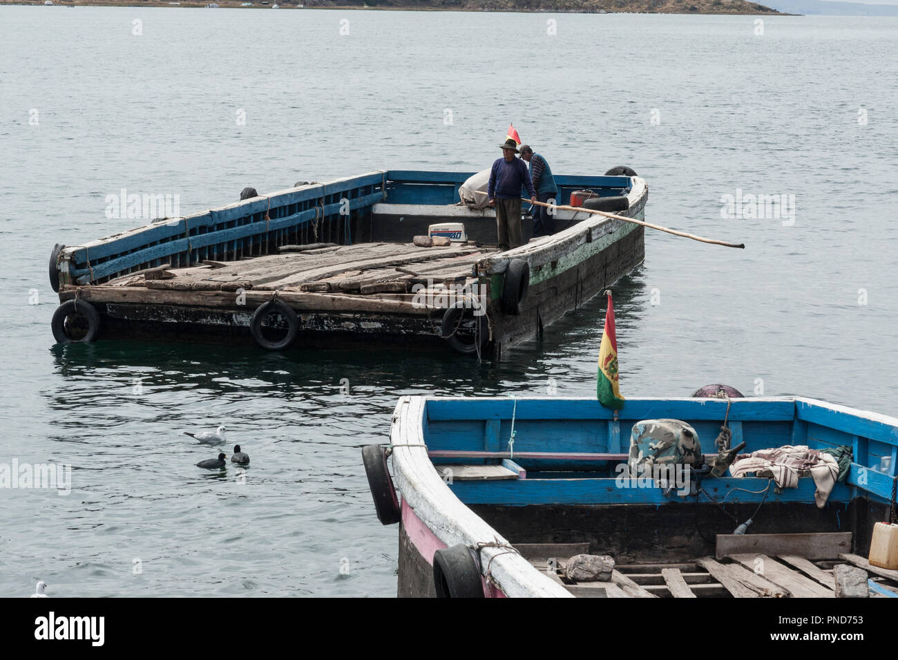SAN PEDRO DE TIQUINA, BOLIVIA - AUGUST 18, 2017: Unidentified indigenous men on a river ferryboats on the shore of Lake Titicaca at the Strait of Tiqu - Stock Image