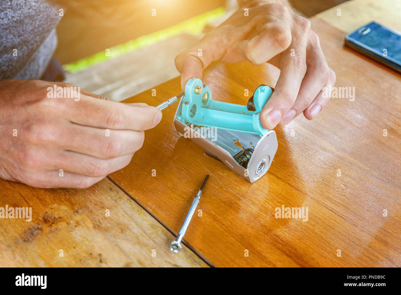Man hands fixing modern vaporizer e-cig gadget to vape e-liquid. Maintenance of electronic equipment mech mod vaping device. Vaper device repair servi - Stock Image