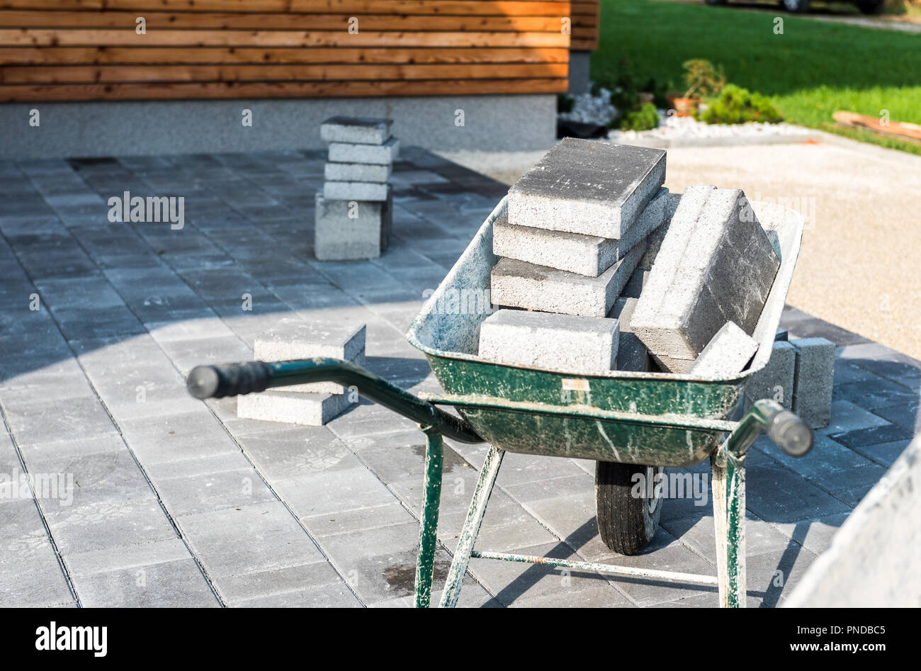 Laying Gray Concrete Paving Slabs In House Courtyard Driveway Patio.  Wheelbarrows Loaded With New Tiles Or Slabs For Driveway, Sidewalk Or Patio  On Le