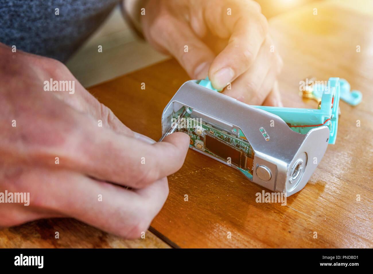 Man hands fixing modern vaporizer e-cig gadget to vape e-liquid. Maintenance of electronic equipment mech mod vaping device. Vaper device repair servi - Stock Image