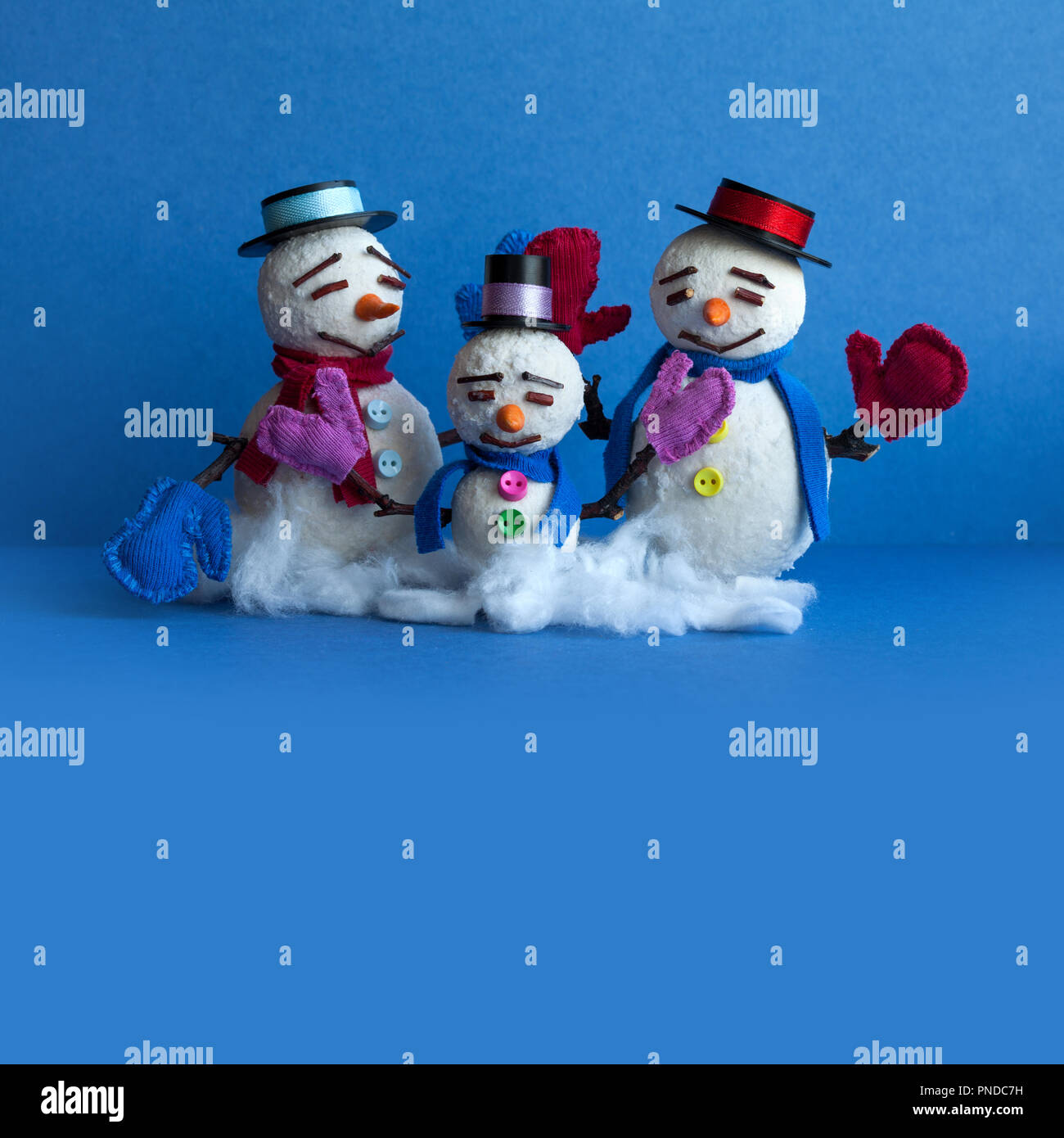 Snowmen family on blue background. Xmas comical snowman characters with mittens scarves and funny hats. Copy space - Stock Image