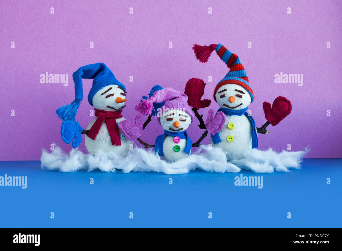 Snowmen family on blue purple background. Xmas comical snowman characters with mittens scarves and funny hats. Copy space - Stock Image