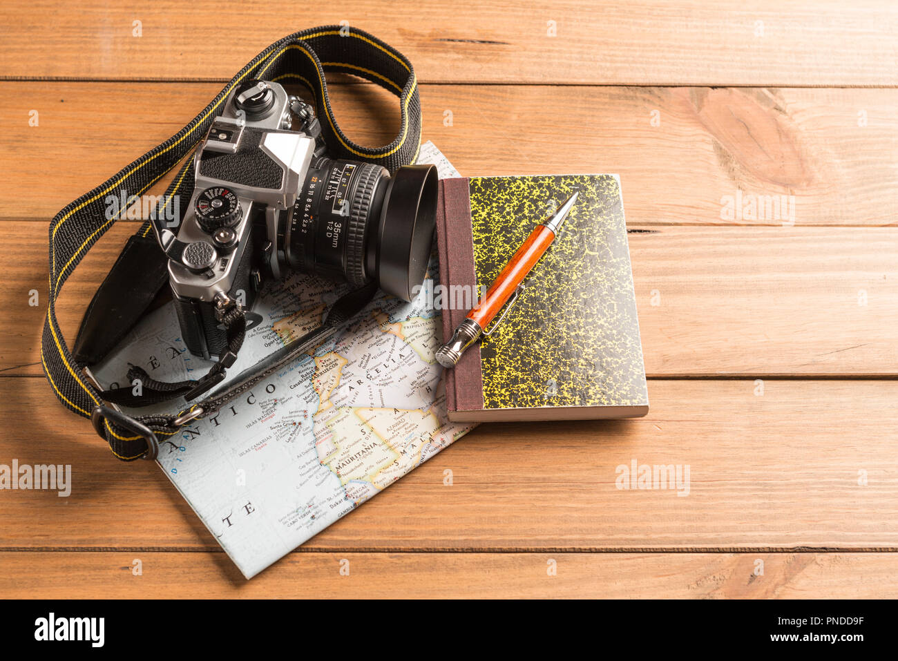 Travel concept. Camera, map, notebook and ball pen on wooden table - Stock Image