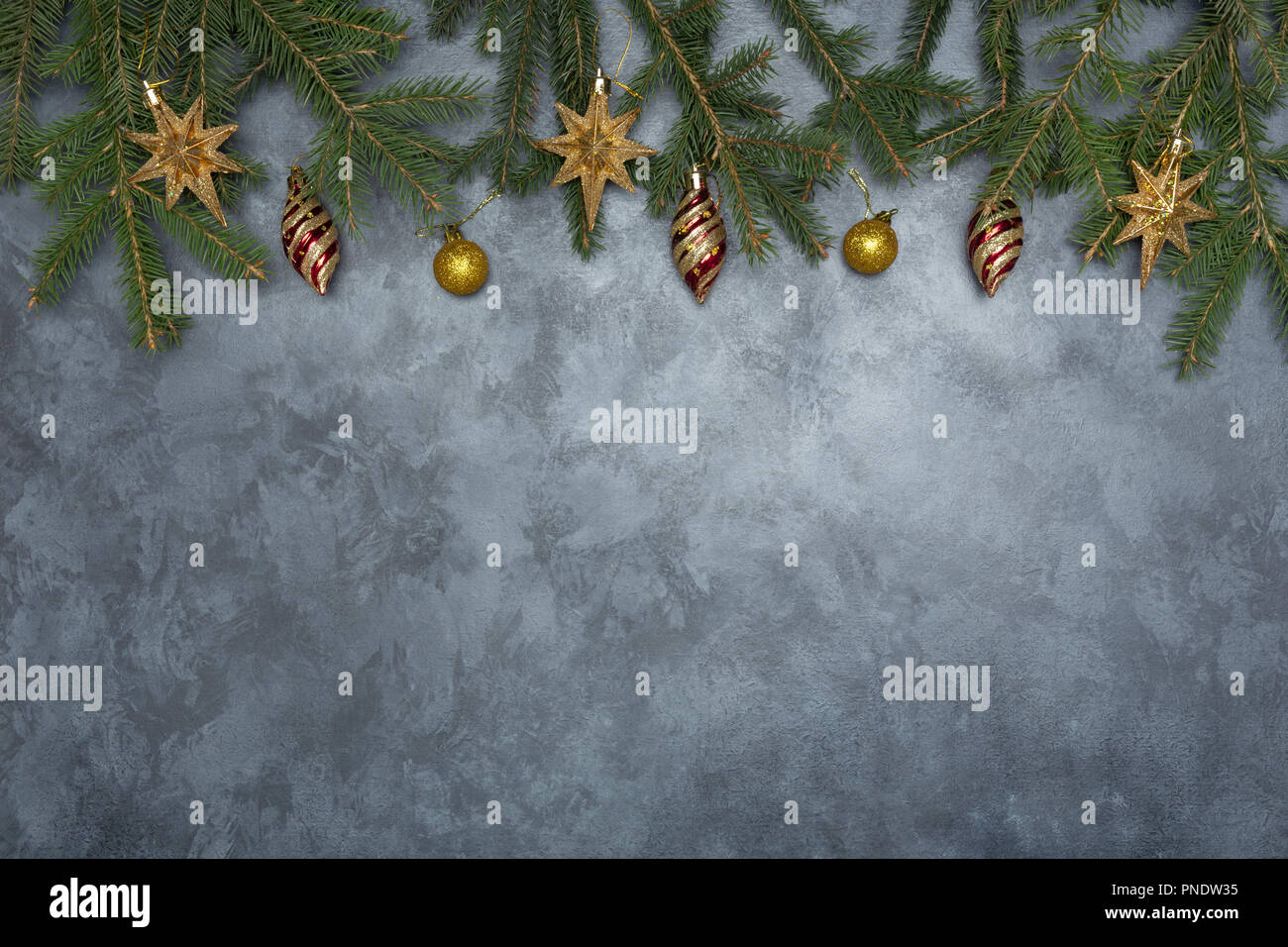 holiday frame of christmas decorations on blue dark stucco concrete background with fir branch gold balls stars christmas socks and toys - Teal And Gold Christmas Decorations