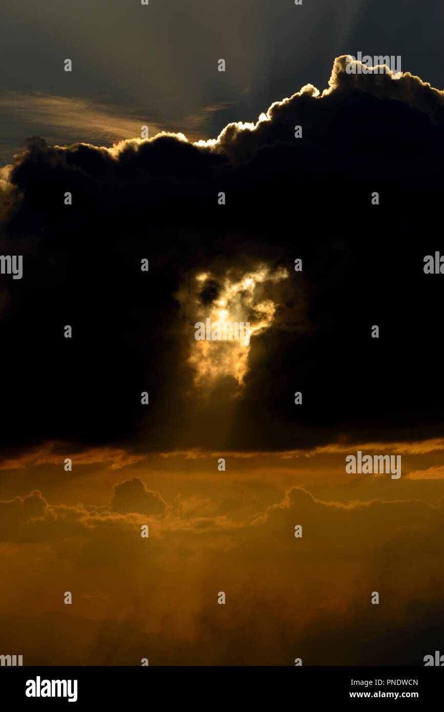 Sunbeams piercing a cloud - Stock Image