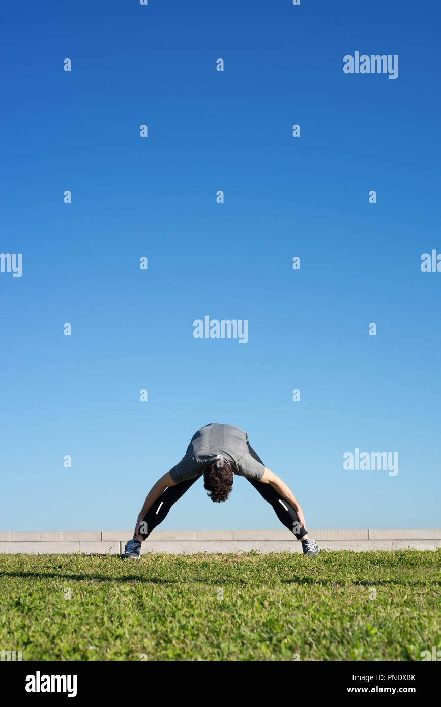 Man doing strechings before running space for text up - Stock Image
