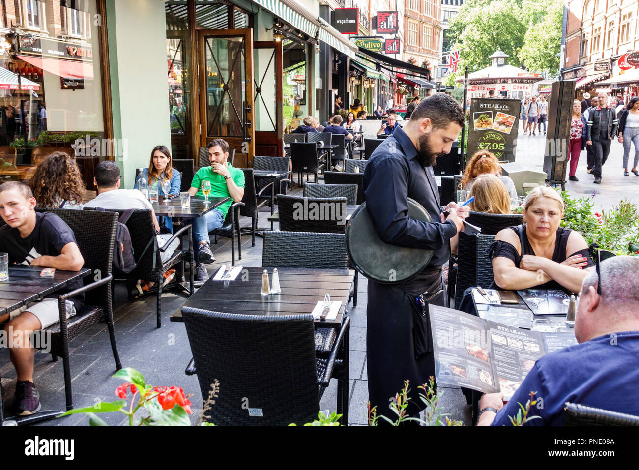 London England Great Britain United Kingdom Leicester Square Steak & Co. restaurant alfresco dining brasserie waiter writing order man woman couple ou Stock Photo