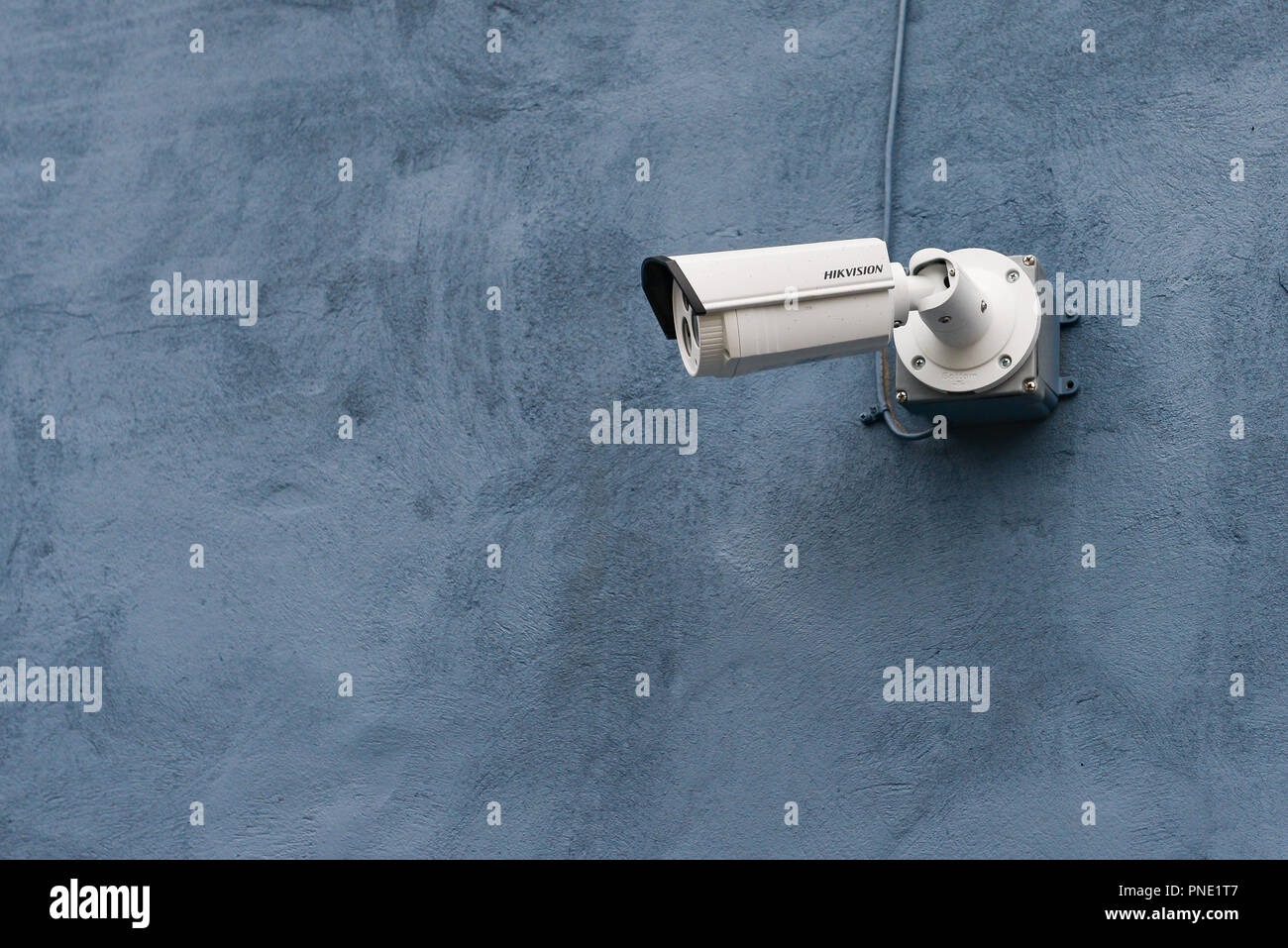 A Hikvision video surveillance camera mounted on a blue exterior wall of a building. - Stock Image