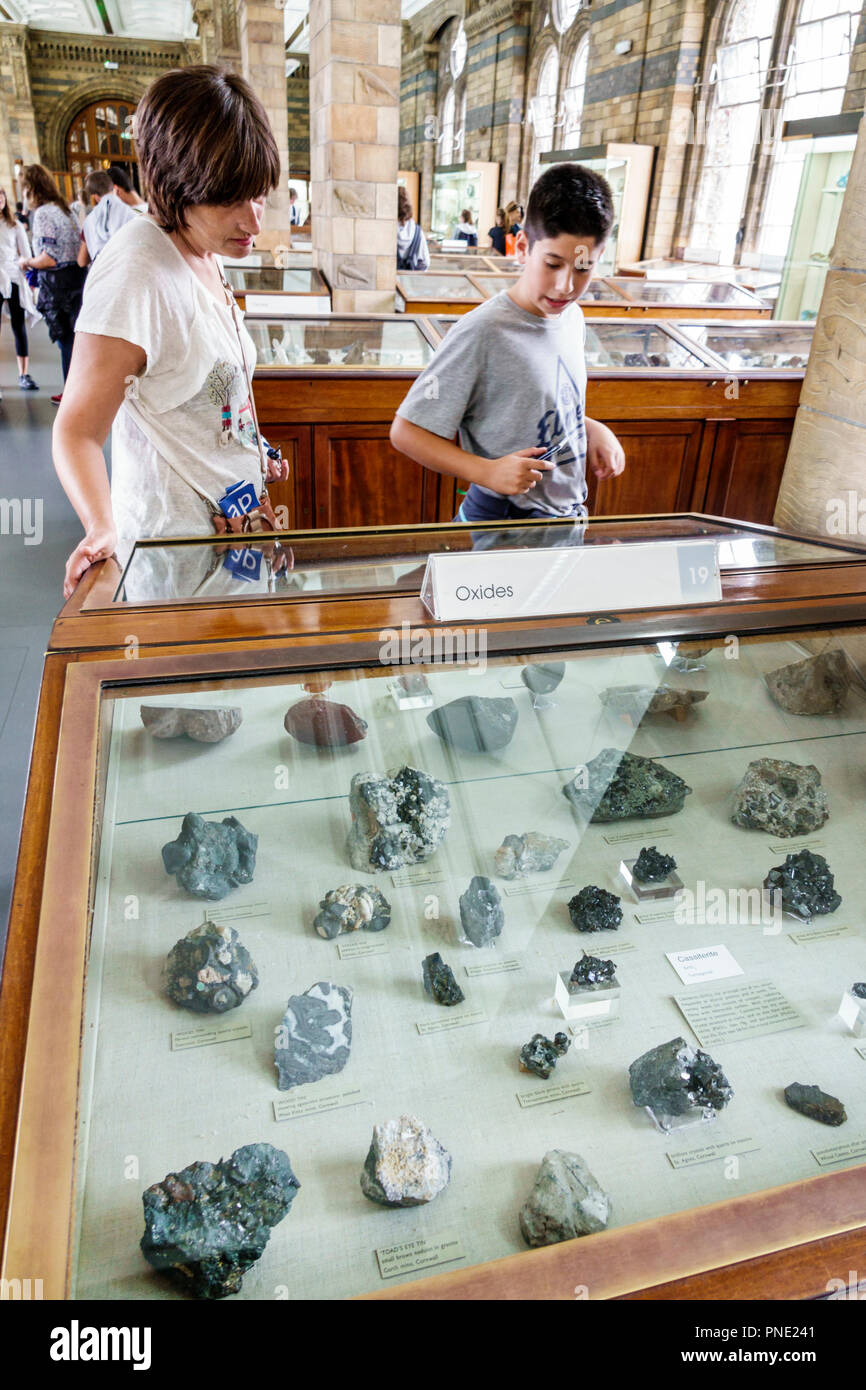 London England Great Britain United Kingdom Kensington Natural History Museum inside minerals exhibit gallery OOxides woman boy tween teen mother son - Stock Image