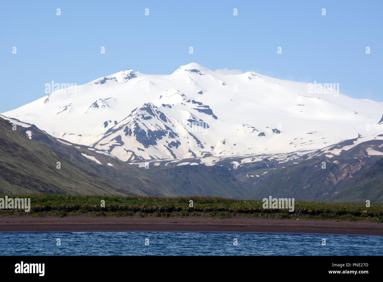 Makushin volcano, an ice covered and active stratovolcano on the island of Unalaska in the Aleutian Islands chain, southwest Alaska. - Stock Image
