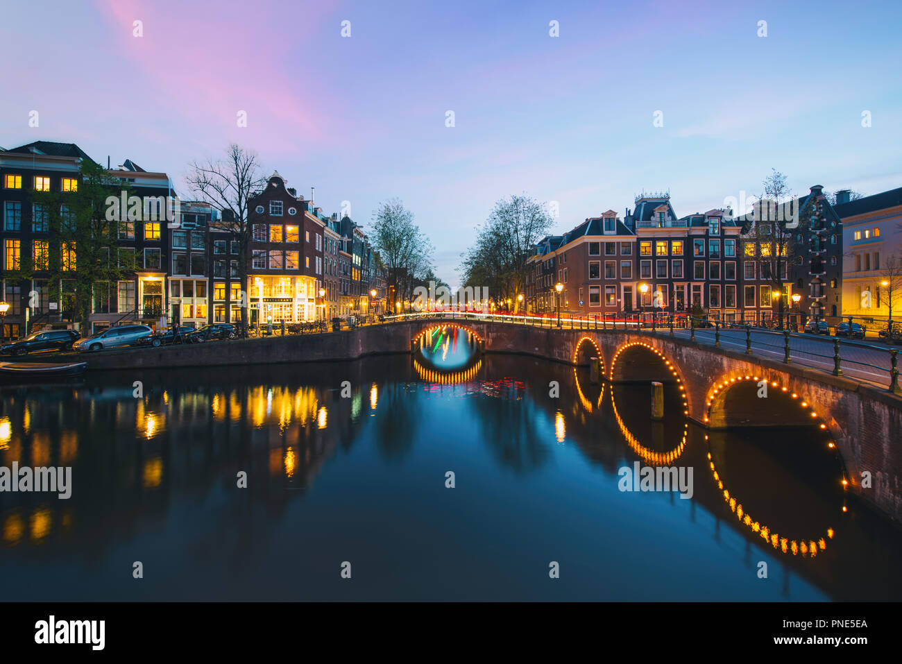 Night city view in Amsterdam, Netherlands. Canal and typical dutch houses at night in Amsterdam, Netherlands - Stock Image