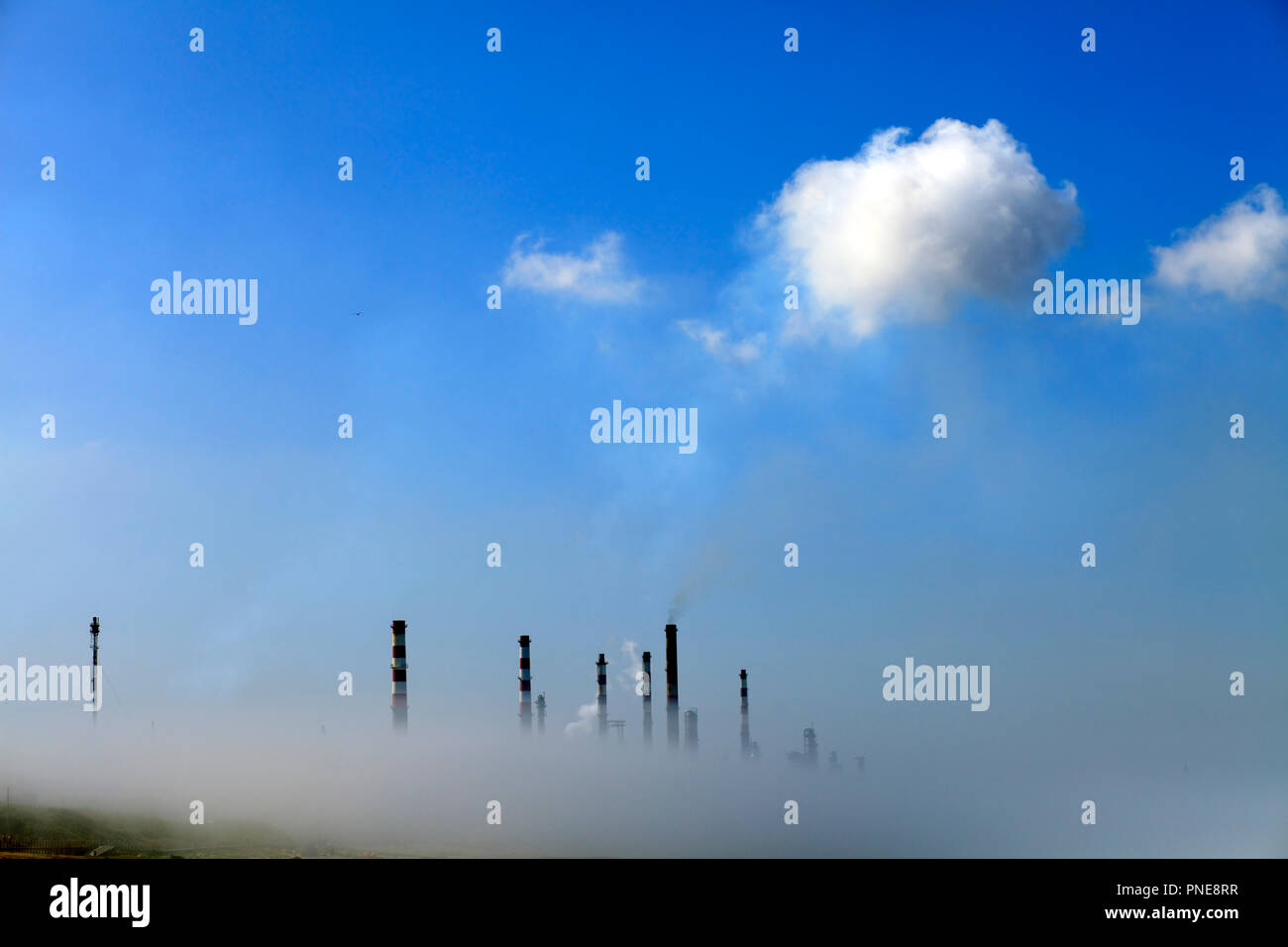 Chimneys of an oil refinery semi losted in smog - Stock Image