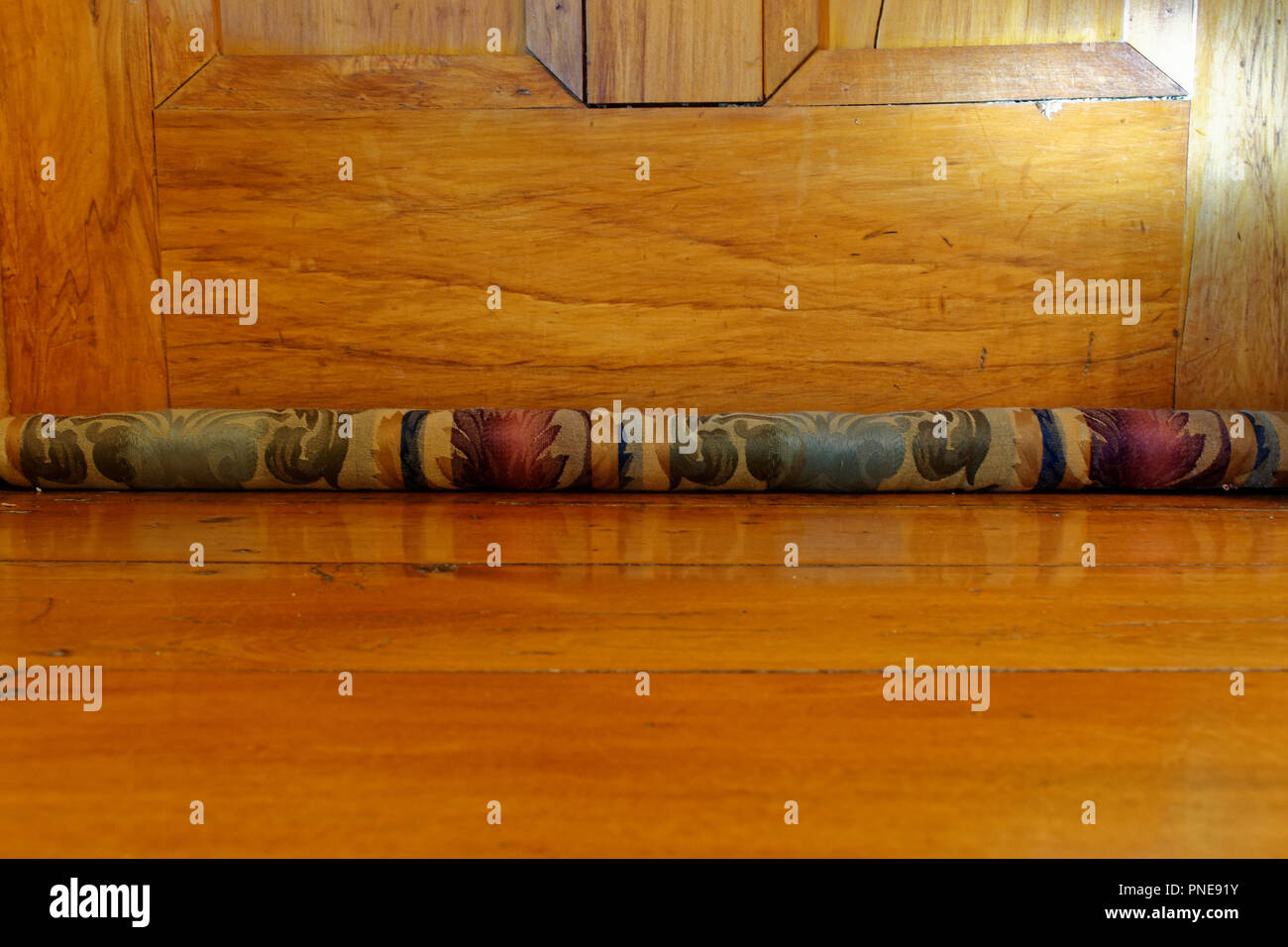 A floral, material draught excluder stops draughts breezing under the door, a simple solution to staying warm in winter. - Stock Image