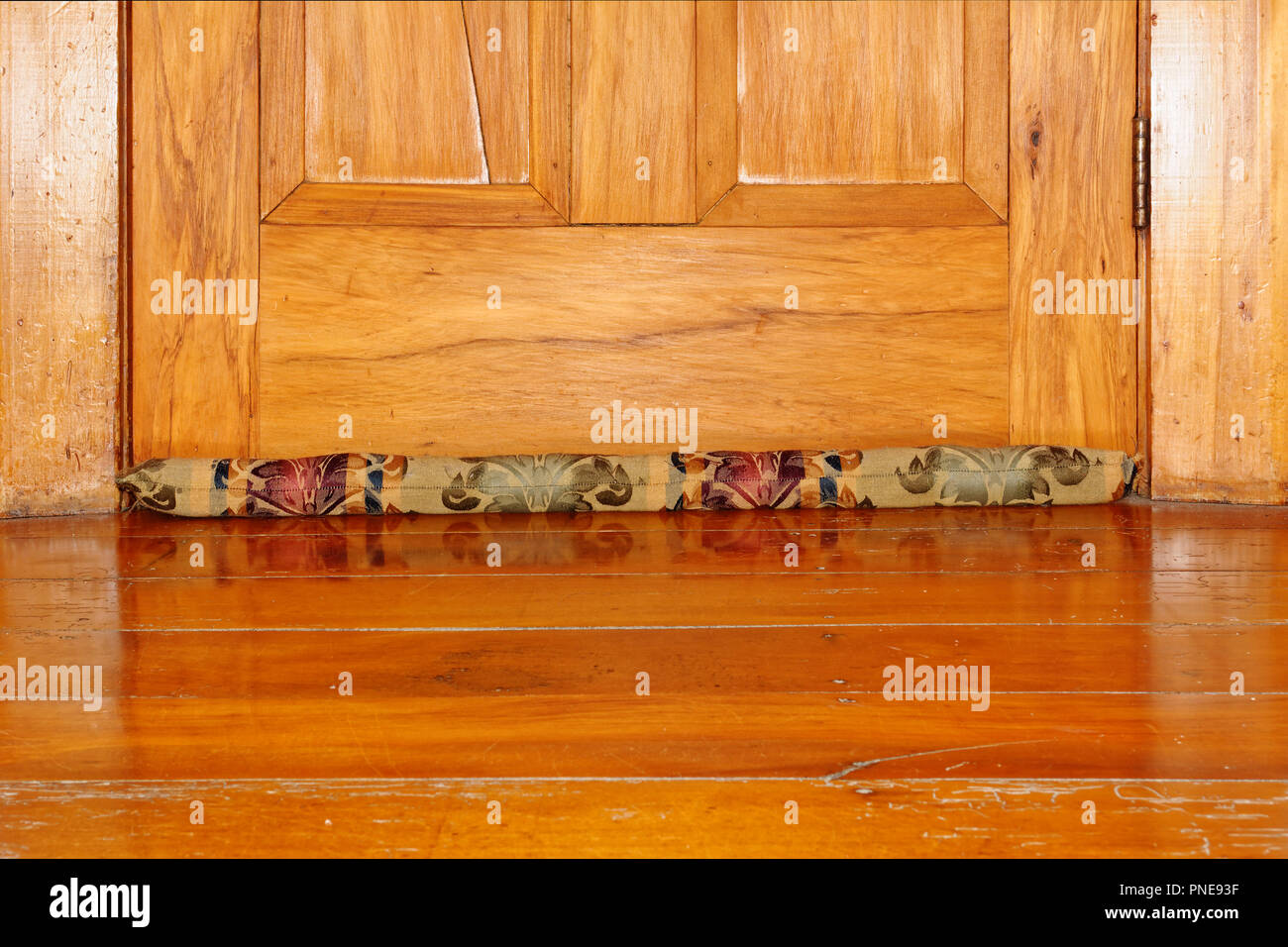 Draught excluder on wooden floor - Stock Image