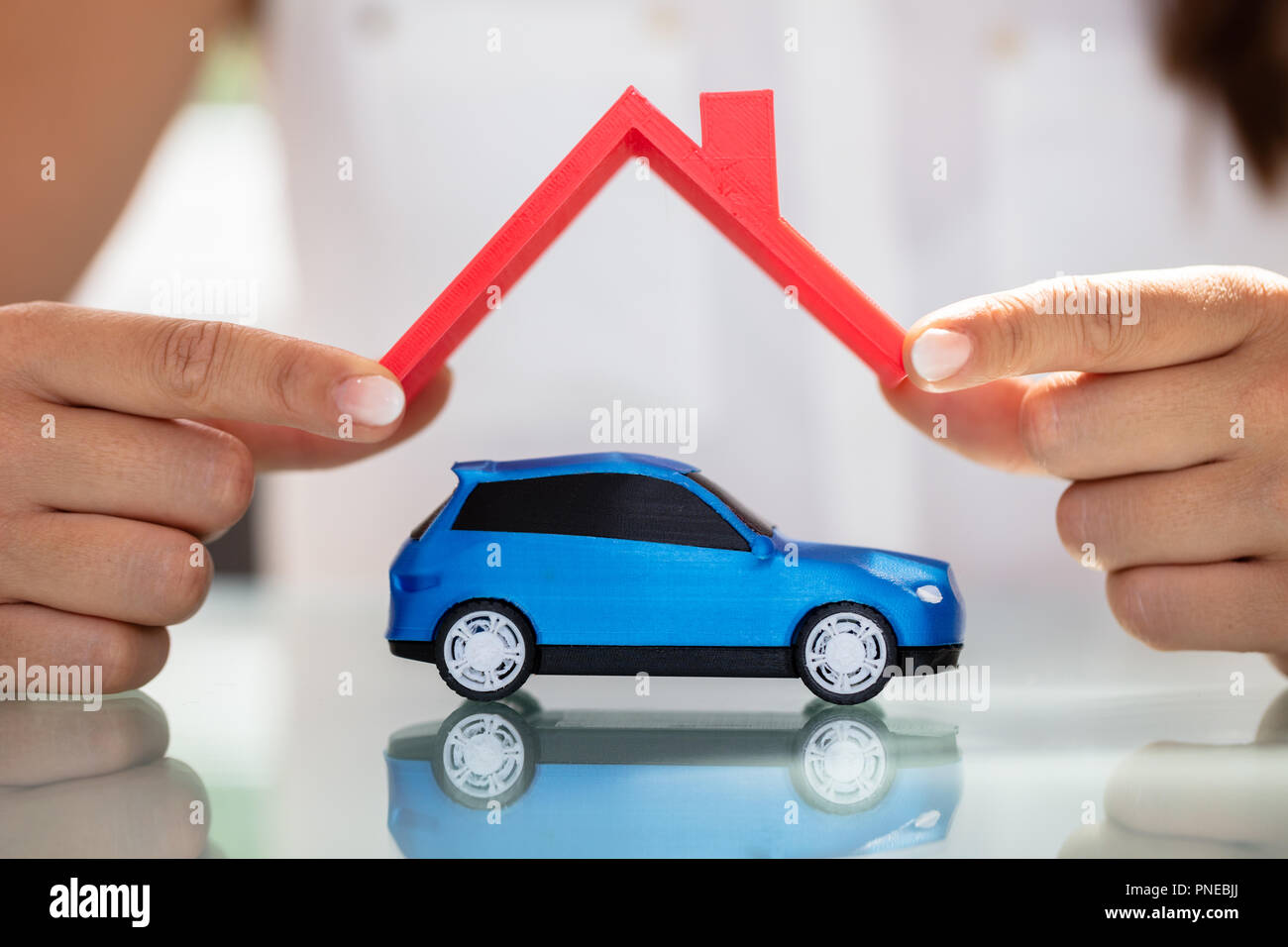 Close-up Of A Businesswoman's Hand Holding Roof Over Blue Car - Stock Image