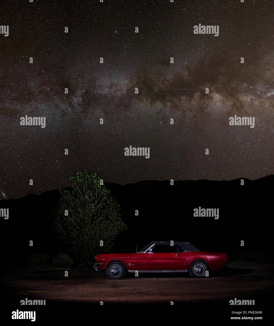 1965 Red Convertible Ford Mustang under the Milky Way at Night - Stock Image