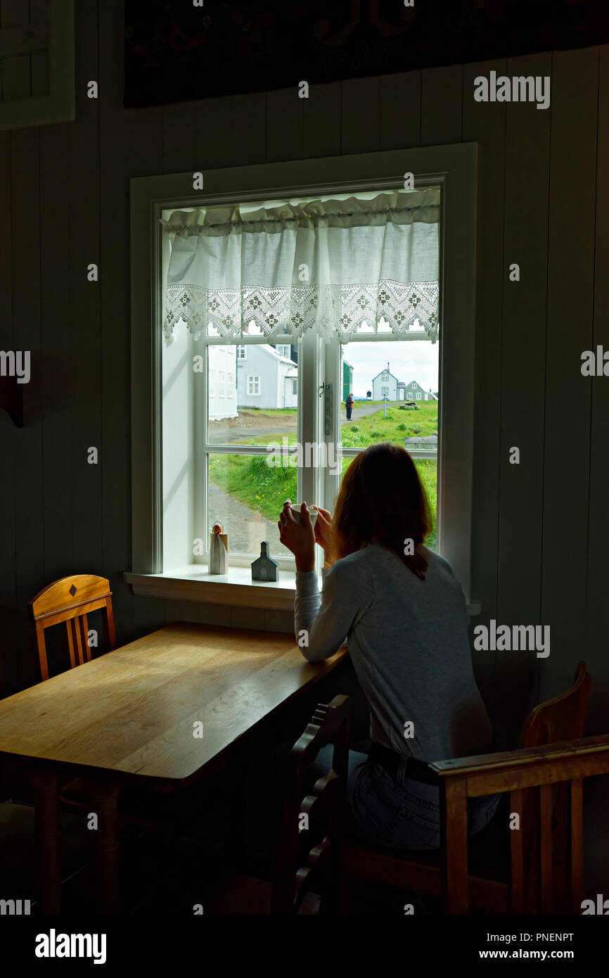 Woman sitting at table looking out through window holding a cup of coffee, Flatey Island, Westfjords, Iceland, Europe. - Stock Image