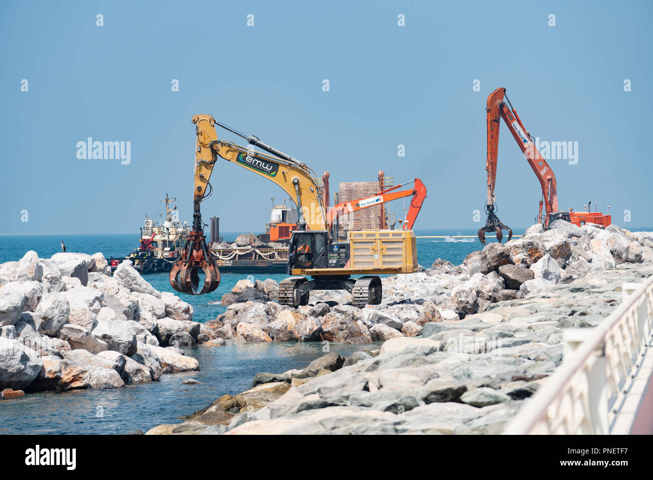 Sea defence construction work by placed large stones on shore on The Palm Jumeirah island in Dubai , United Arab Emirates, UAE. - Stock Image