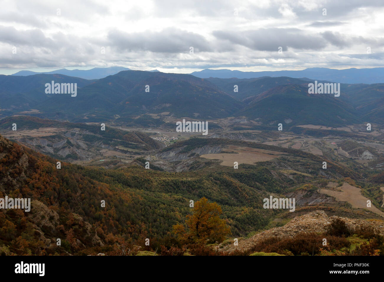 Blue cloudy sky and typical mountains and hills covered with forest met in autumn while hiking from Yebra de Basa town to Santa Orosia church, Spain Stock Photo