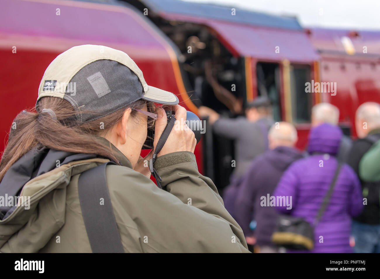 Kidderminster, UK. 21st September, 2018. Day Two of Severn Valley Railway's Autumn Steam Gala sees excited trainspotters flocking to the platform at Kidderminster SVR vintage station. Despite the rain showers, train enthusiasts take every opportunity to get as close as they can to these magnificent UK steam locomotives, particularly the Duchess of Sutherland looking resplendent in her fine crimson livery. A female photographer (rear view) is seen taking photographs of the busy platform scene at this heritage railway. Credit: Lee Hudson/Alamy Live News Stock Photo