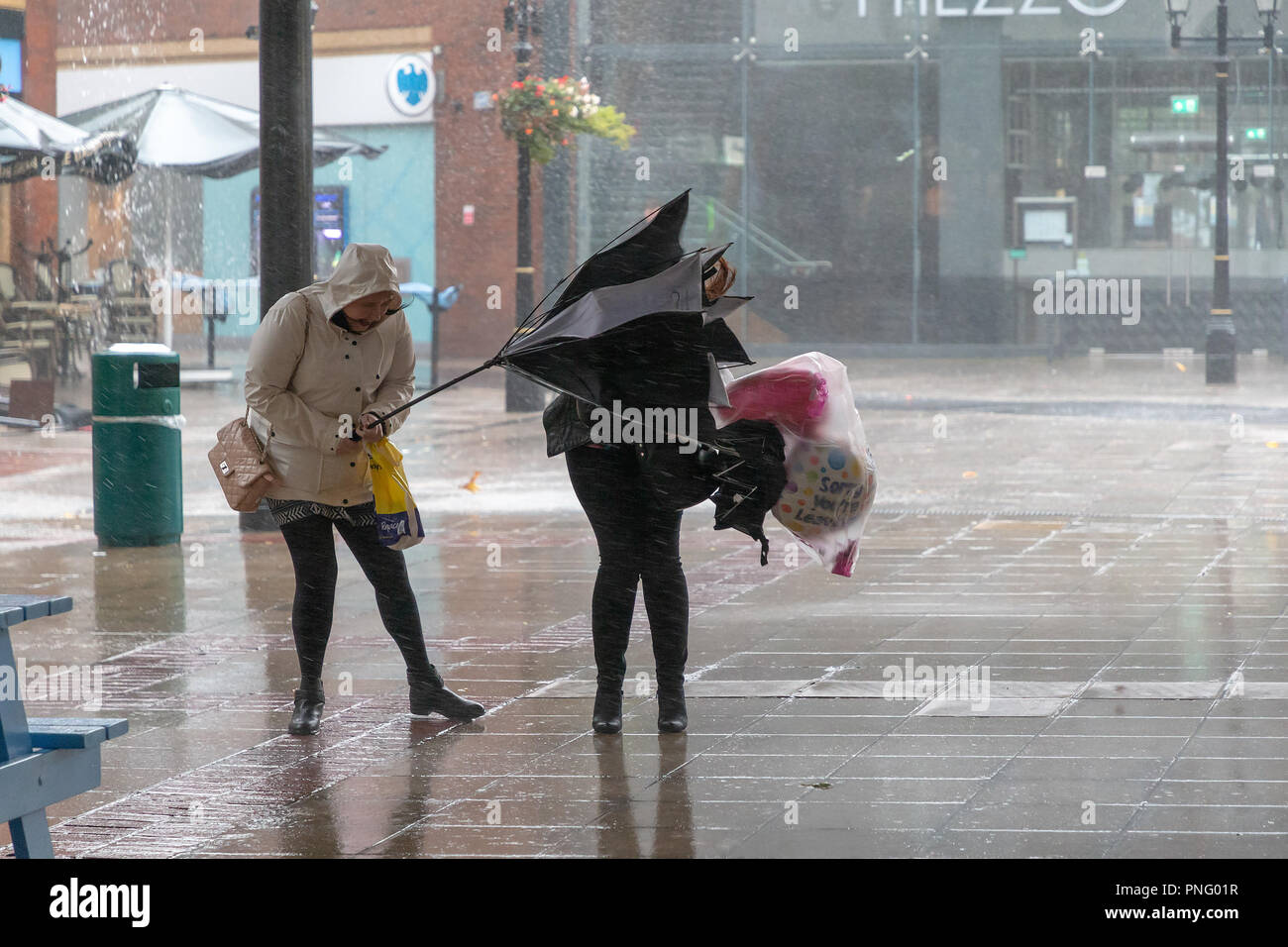 Warrington Town Centre, Cheshire, England, UK - 21 September 2018 - Weather -  Late afternoon and the gale force winds of Storm Bronagh,  the second storm of the UK winter within days, increased their intensity, with gusts of over 50mph in Warrington, Cheshire. Pictured: People struggle to keep their umbrellas the right way round in the strong winds - Stock Image