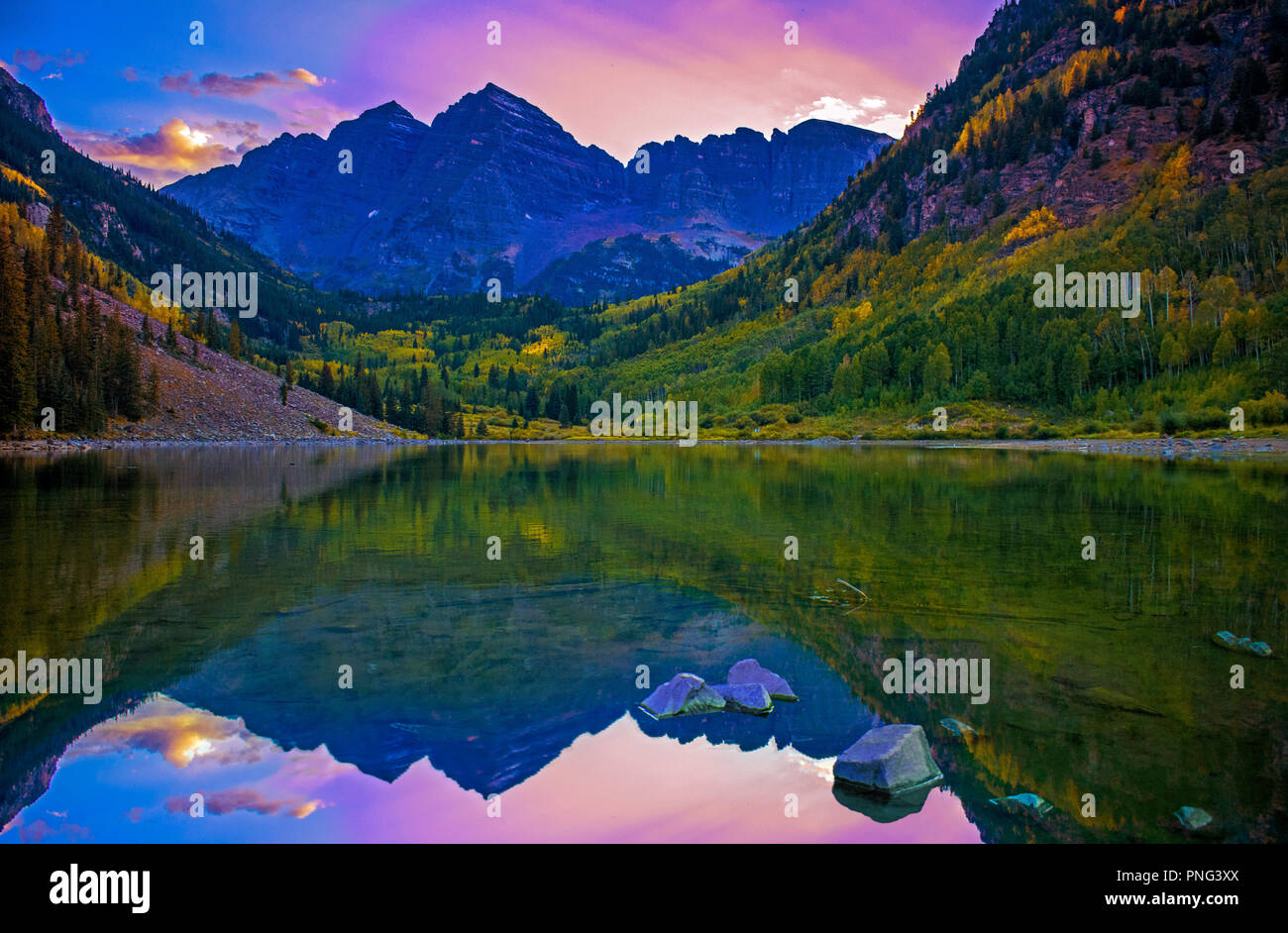 Epic mountain peaks during sunset and colorful skies reflect in placid lake in autumn. - Stock Image