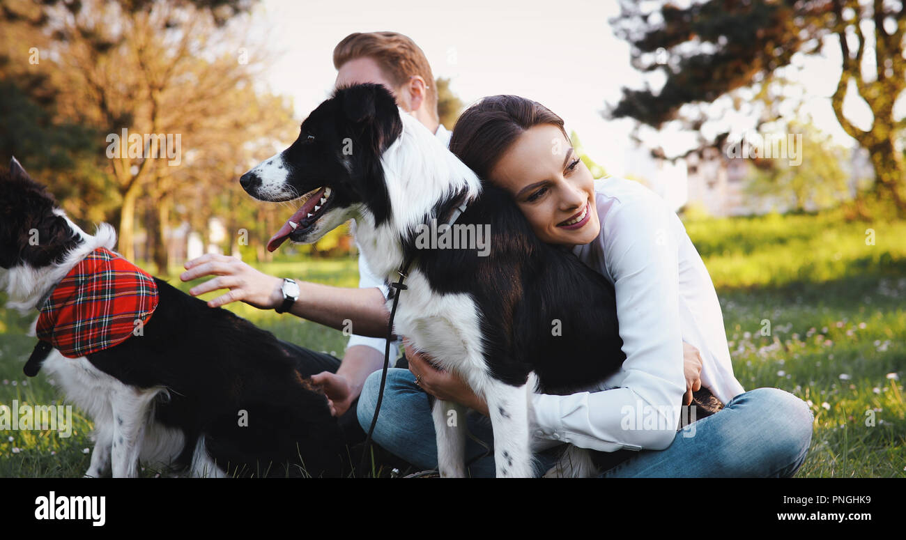 Beautiful couple walking dogs and bonding in nature - Stock Image
