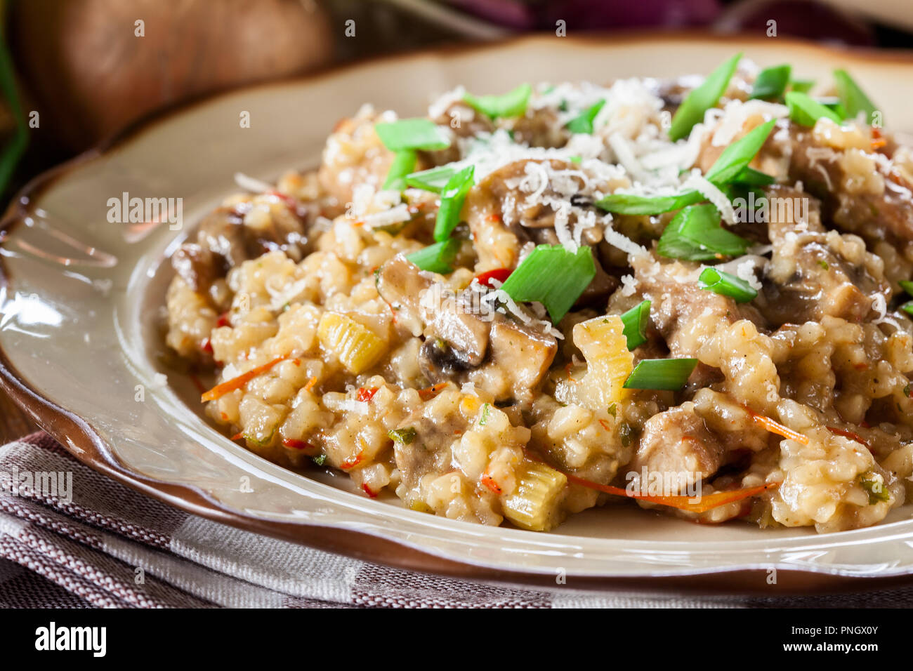 Risotto with champignon mushrooms, pork and parmesan. Italian cuisine - Stock Image