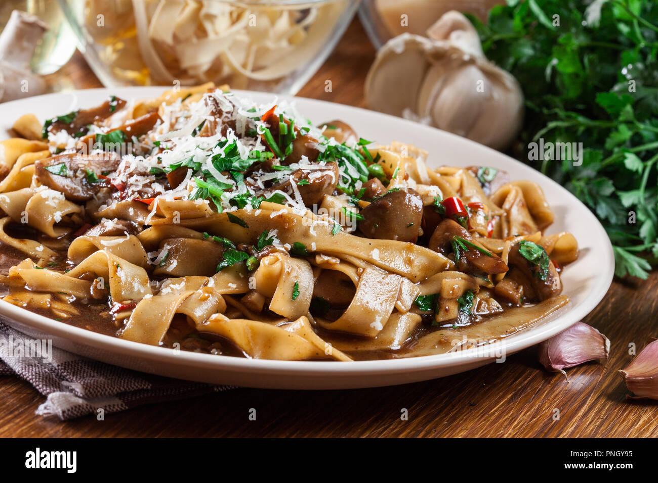 Tagliatelle pasta with champignon in mushroom gravy. Italian dish - Stock Image