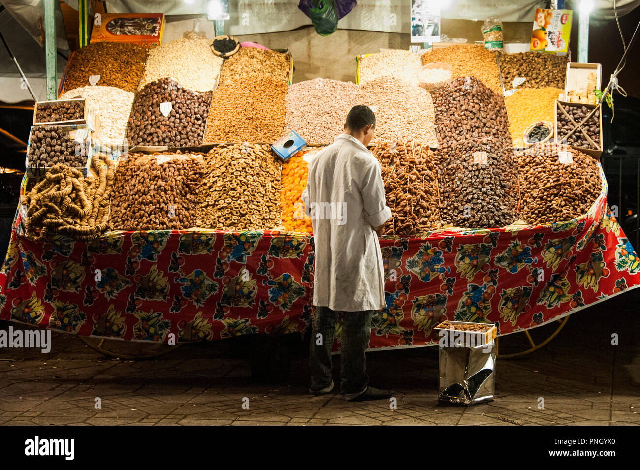 25-02-11. Marrakech, Morocco. A stall holder selling dates and dried apricots in Jemaa el-Fna at night. It is a large public square with small merchan - Stock Image