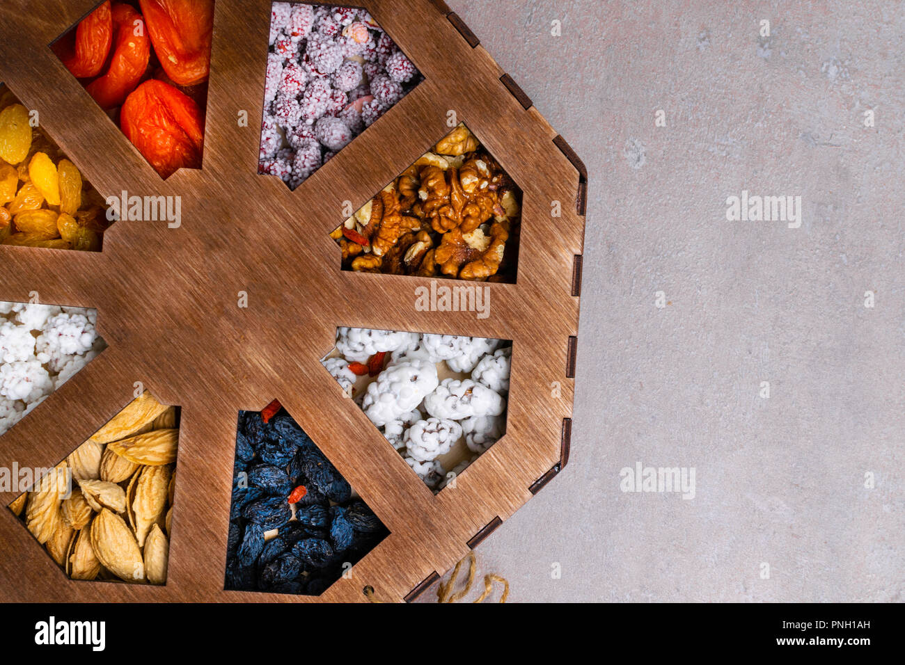 Mixed Nuts on grey background, as apricot, raisins, walnuts, goji, peanuts in glaze, almonds Healthy food and snack. vitamins, fiber, pectin, iron, po Stock Photo