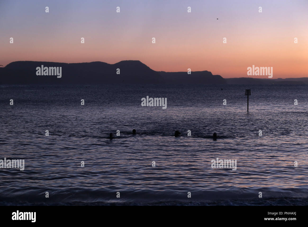 swimmers silhouetted in a winter sea at sunrise - Stock Image