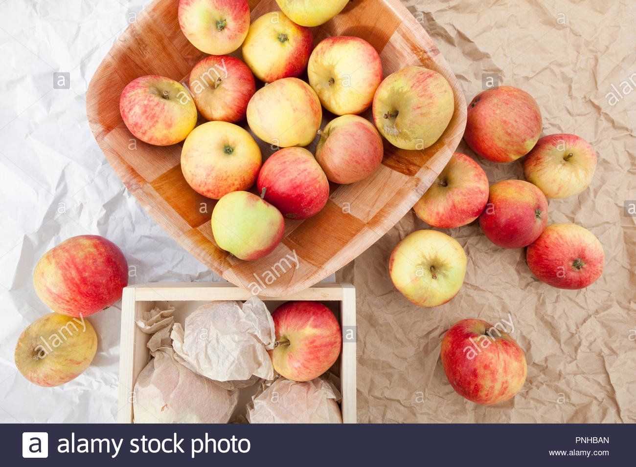 Apples in boxes - some wrapped and ready for storing - Stock Image