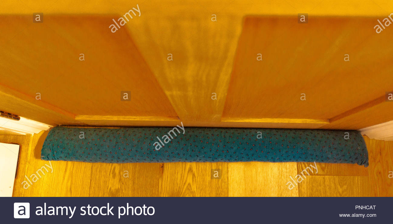 A green patterned draught excluder - Stock Image