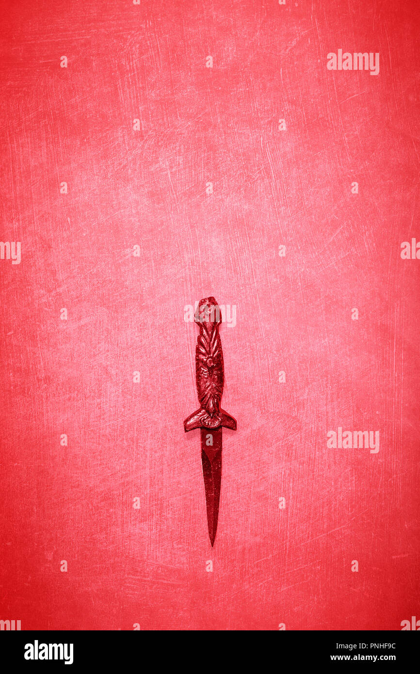 Red Wicca wiccan dagger on a red textured background with space for copy and text.  Ceremonial blade for spiritual rituals - Stock Image