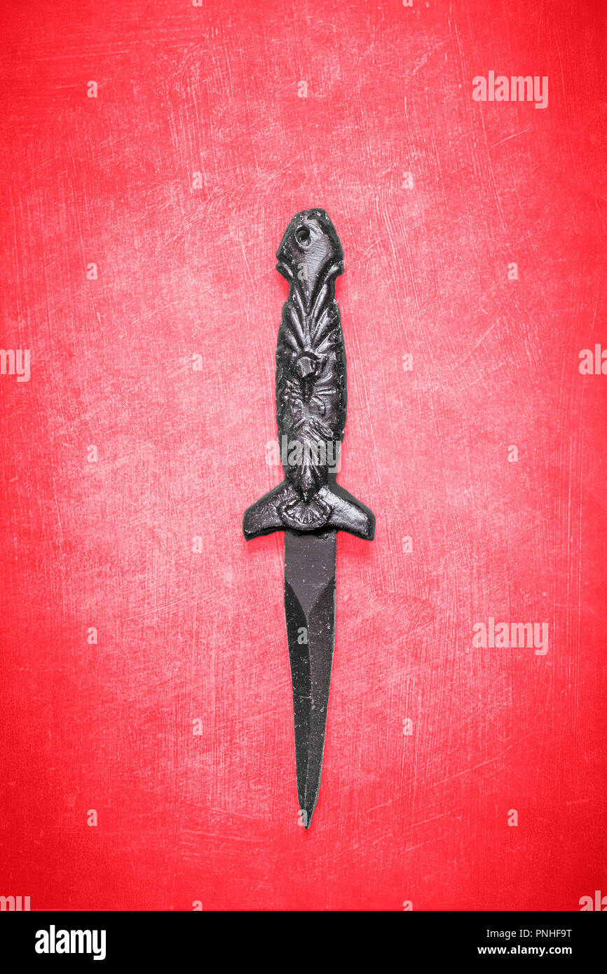 Black Wicca wiccan dagger on a textured red background with space for copy and text.  Ornamental dagger for religious and spiritual ceremony - Stock Image