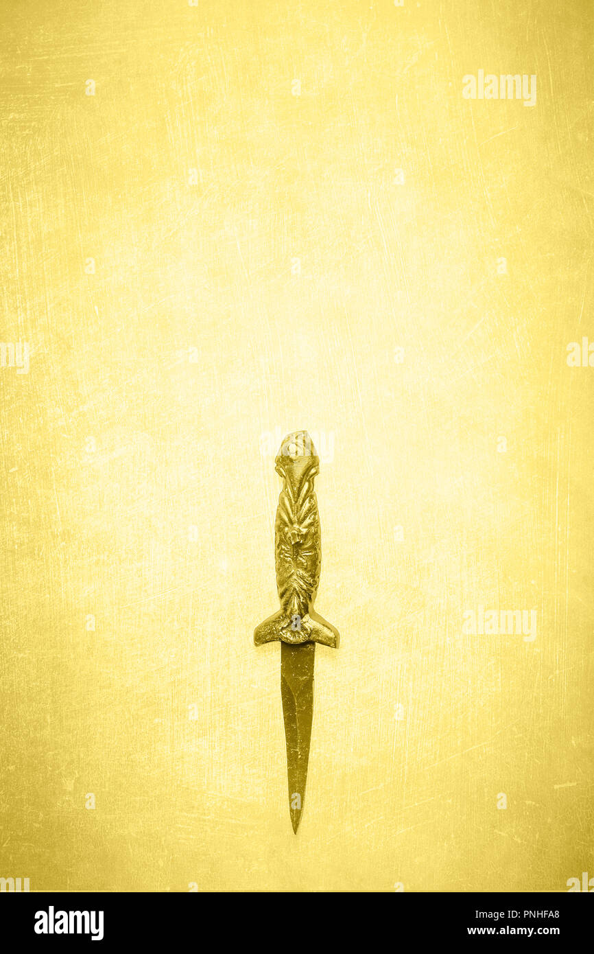 Black wicca wiccan dagger on a textured yellow background.  Ceremonial blade for use in religious and spiritual rituals. - Stock Image