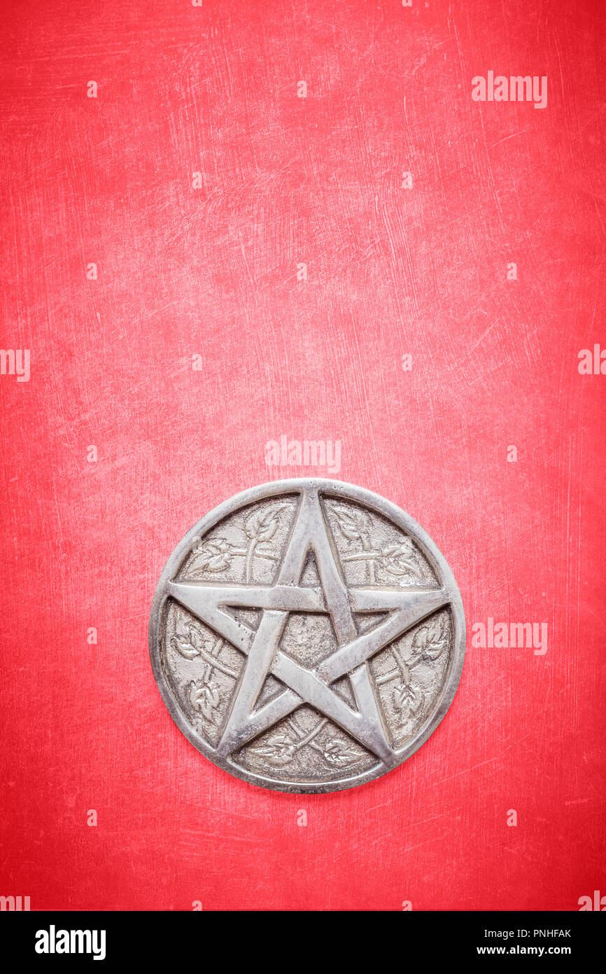 Siver pentagram on a textured red background.  Pentagram for wicca wiccan ceremony and spiritual rituals - Stock Image